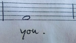 """Detailfoto van stukje notenbalk, met daarop een enkele noot en daaronder de handgeschreven tekst: """"you."""""""